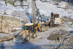 MOSKOU, FEBRUARI 01, 2018: De wintermening over vuil zwaar bouwmateriaal, voertuigenarbeiders op het werk Het boren verrichtingen Stock Fotografie