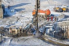 MOSKOU, FEBRUARI 01, 2018: De wintermening over vuile zwaar bouwmateriaal, voertuigen en arbeiders op het werk Het boren de verri Stock Foto