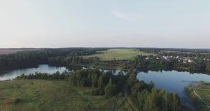 Moskou Oblast, Rusland De camera vliegt over de groene weiden, aan bossen en blauwe meren stock videobeelden