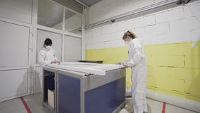 Moskou, Rusland - April, 2019: Arbeiders opgepoetst kader bij fabriek actie Twee vrouwen in het witte malen van overallarbeiders stock video