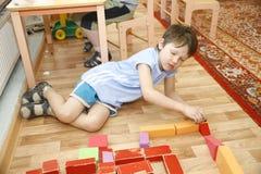 MOSKOU, 17 RUSLAND-APRIL, 2014: de kinderen spelen met speelgoed en nemen de privé-leraar in een kleuterschool in dienst Stock Afbeelding