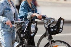 MOSKOU, RUSLAND - APRIL 30, 2018: Een groep van twee meisjes bevindt zich met gehuurde fietsen op de stoep Hoofdstadcentrum Royalty-vrije Stock Foto