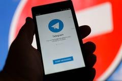 MOSKOU, RUSLAND - APRIL 16, 2018: Een mobiele telefoon met het Telegram app ter beschikking tegen een verbiedend teken Telegram i stock fotografie