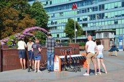 Moskou, Rusland, 11 Augustus, 2018 De mensen in huuragentschap van elektrische autopedden op Trubnaya regelen in Moskou stock fotografie