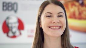 MOSKOU, RUSLAND - CIRCA November 2017: Jonge aantrekkelijke vrouw die camera in KFC-restaurant bekijken stock footage