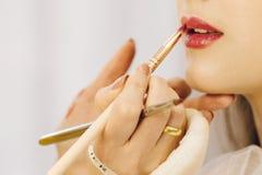 Moskou Rusland - 11 13 2018: De make-upkunstenaar past de lippenstift door borstel op lippen van een jonge vrouw toe De schoonhei stock foto's