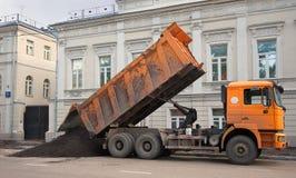 Moskou, Rusland De oranje vrachtwagen dumpte heet asfalt op de rijweg van de straat De werken van de weg royalty-vrije stock foto