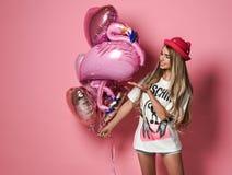 MOSKOU, RUSLAND, DECEMBER 2018 - Goed gevormd meisje die in witte t-shirt en leuke hoed kleurrijke ballons voor partij houden royalty-vrije stock afbeelding