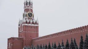 MOSKOU, RUSLAND - DECEMBER, 2018: Schuine stand neer van de klokketoren van Spasskaya en de muur van Moskou het Kremlin op de win stock videobeelden