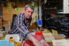 Moskou, Rusland - Februari 25, 2017: De grijs-haired mensenverkoper van naar huis geproduceerde honing bij de markt zet de goeder Stock Foto's