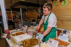 Moskou, Rusland - Februari 25, 2017: De jonge verkoper in een groene schort bij de markt vult een kruik met honing voor de koper Royalty-vrije Stock Foto