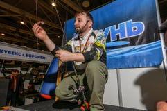 Moskou, Rusland - Februari 25, 2017: De professionele visser bevordert wobblers en de uitrustingen op de speciale visserij tonen Stock Foto's