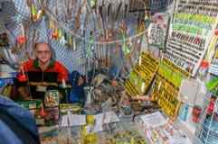 Moskou, Rusland - Februari 25, 2017: Verkoper van vissen-aas achter een teller met wobblers en kunstmatige insecten Royalty-vrije Stock Foto
