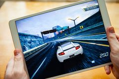 Moskou/Rusland - Februari 25, 2019: Witte ipad ter beschikking Voor het scherm, de spelbehoefte aan snelheid royalty-vrije stock afbeelding