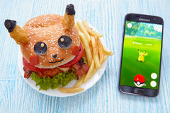 Moskou, Rusland - Juli 29, het Redactiebeeld van 2016: De ventilator Art Pikachu Burger en Smartphone met Pokemon gaat toepassing Royalty-vrije Stock Afbeeldingen