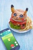 Moskou, Rusland - Juli 29, het Redactiebeeld van 2016: De ventilator Art Pikachu Burger en Smartphone met Pokemon gaat toepassing Stock Afbeelding