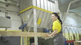 Moskou, Rusland - Juni 15, 2018: De arbeider zet houten raad in machine actie De vrouwenarbeider verbetert gemakkelijk en stapelt stock videobeelden