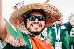 MOSKOU, RUSLAND - JUNI 2018: Een gelukkige Mexicaanse ventilator met een vlag en sombrero tijdens de Wereldbeker van FIFA stock fotografie