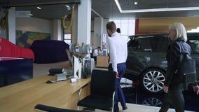 MOSKOU, RUSLAND - mag, 2018: De verkoper ontmoet klant in het handel drijven voorraad Vrouw bij autohandelaar stock footage