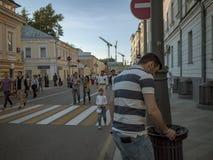 MOSKOU, RUSLAND - MEI 9, 2016: Een mens in een gestreept polo zet uit een sigaret op de rand van een urn rond de Straat van Bolsh Stock Foto