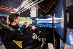 MOSKOU, RUSLAND - OKTOBER 27 2018 Simulatie van het spel van de raceauto videospeler met grote het schermmonitors en cockpitcontr royalty-vrije stock foto's