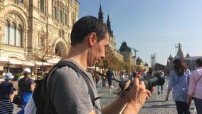 Moskou, Rusland - September 5, 2018: De gelukkige jonge mens maakt een foto op Rood Vierkant in Moskou, Rusland, levensstijl, rei stock videobeelden