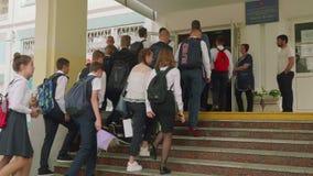 MOSKOU - SEPTEMBER 1, 2018: Teenagedkinderen in eenvormig met rugzakken en zakken dichtbij school eerst van september stock videobeelden