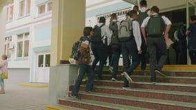 MOSKOU - SEPTEMBER 1, 2018: Teenagedkinderen in eenvormig met rugzakken en zakken dichtbij school eerst van september stock footage