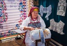 Moskou, Victory Park, 11 Juni 2018: Een bejaarde in Russisch nationaal kostuum nam in traditionele ambacht in dienst stock afbeeldingen