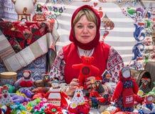 Moskou, Victory Park, 11 Juni 2018: vrouw in Russisch nationaal kostuum die traditionele poppen in het Park verkopen stock foto's