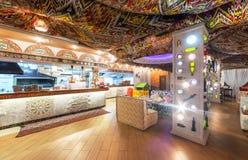MOSKVA - AUGUSTI 2014: Östlig restaurang för inre Chaihana vardagsrum i en traditionell stil Den huvudsakliga matsalen med en öpp Arkivbild