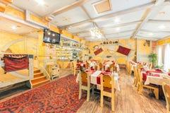 MOSKVA - AUGUSTI 2014: Inre av restaurangen Hall av gul färg som dekoreras i en stil för bonde` s Arkivfoto