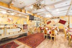 MOSKVA - AUGUSTI 2014: Inre av restaurangen Hall av gul färg som dekoreras i en stil för bonde` s Arkivbild