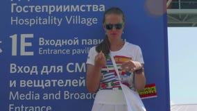 Moskva - Circa Juli, 2018: Den Valunteer flickan på styltor underhåller fotbollsfan för fotbollsmatch i Luzhnkik stadion lager videofilmer
