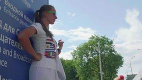 Moskva - Circa Juli, 2018: Den Valunteer flickan på styltor underhåller fotbollsfan för fotbollsmatch i Luzhnkik stadion stock video