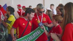 MOSKVA - CIRCA JULI, 2018: Kamerabesättningen av spanjorkanalen intervjuar fans från Spanien för fotbollsmatch lager videofilmer