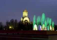 Moskva, elektrisk springbrunn och St George kyrka Arkivfoto