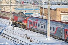 MOSKVA FEBRUARI 01 2018: Övervintra sikten på den ryska järnväg diesel- lokomotivet som drar passagerarelagledare på stångvägbuss Arkivfoto