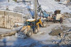 MOSKVA FEBRUARI 01 2018: Övervintra sikten på smutsig tung konstruktionsutrustning, medelarbetare på arbete Borrandeoperationer p Royaltyfri Fotografi