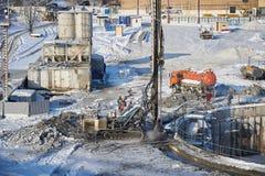 MOSKVA FEBRUARI 01 2018: Övervintra sikten på smutsiga tung konstruktionsutrustning, medel och arbetare på arbete Borrandeoperati Royaltyfria Bilder