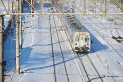 MOSKVA FEBRUARI 01 2018: Sikt för vinterdag på det ryska järnväg passageraredrevet i rörelse För järnvägsspårstång för snö dold v Royaltyfria Bilder