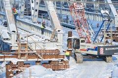 MOSKVA FEBRUARI 01 2018: Sikt på arbetare med larvkranen som bygger en metallbro över stångvägspår Vinterkonstruktion Royaltyfri Foto