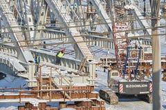 MOSKVA FEBRUARI 01 2018: Sikt på arbetare med larvkranen som bygger en metallbro över stångvägspår Vinterkonstruktion Royaltyfria Foton