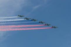 MOSKVA - MAJ 9: Sex stridsflygplan SU-25SL med simbol av Ryssland tre färger av den ryska flaggan ståtar på Arkivfoton