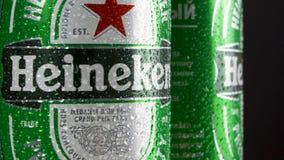 Moskva Ryssland circa mars 2018: Gröna cans för förkylning av populärt holländskt öl med att rotera för Heineken logo stock video