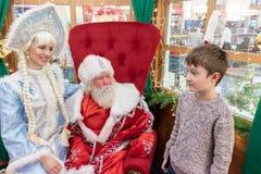 MOSKVA RYSSLAND - DECEMBER 1, 2018: En pojke möter jultomten i hans hus i centrala barn shoppar, för det nya året och julhelgdags royaltyfria bilder