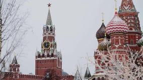 Moskva Ryssland - December, 2018: Lutande upp ultrarapid av St-basilikas domkyrka och det Spasskay tornet i snö på dagsljus arkivfilmer