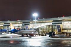 MOSKVA RYSSLAND - 25 december 2017: Nattsikt av terminal A av Vnukovo den internationella flygplatsen och den Sukhoi superjeten a Royaltyfria Foton
