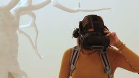 MOSKVA RYSSLAND - DECEMBER 06, 2017: samtida konstutställning, en flicka med ryggsäcken i VR-exponeringsglas med kameran 3d lager videofilmer