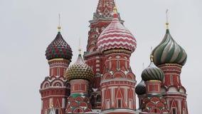 MOSKVA RYSSLAND - DECEMBER, 2018: Vippa p? upp av St-basilikas domkyrka i sn? p? bakgrunden av gr? himmel stock video